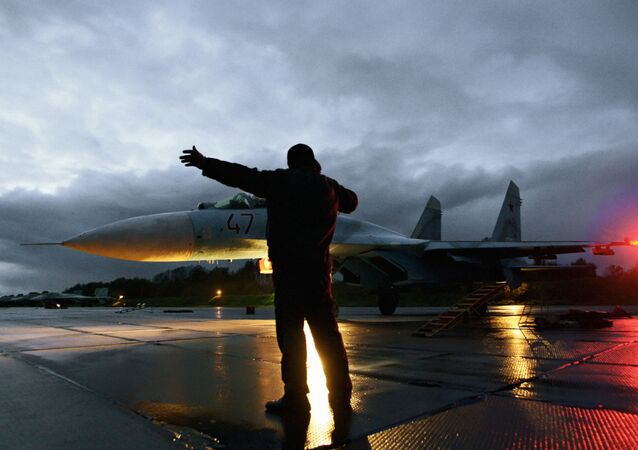 Military technician gives the go-ahead for the take-off of a Su-27 fighter jet