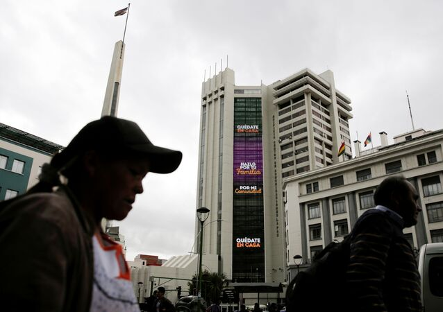 People walk past an electronic sign on the Bolivia's government building displaying the message Stay at home, do it for your family and For my community, as the coronavirus disease (COVID-19) outbreak continues, in downtown La Paz, Bolivia March 20, 2020