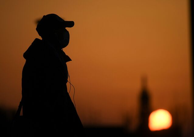 A person wearing a face mask is seen at the sunset as the spread of coronavirus disease (COVID-19) continues, in Milan, Italy March 21, 2020
