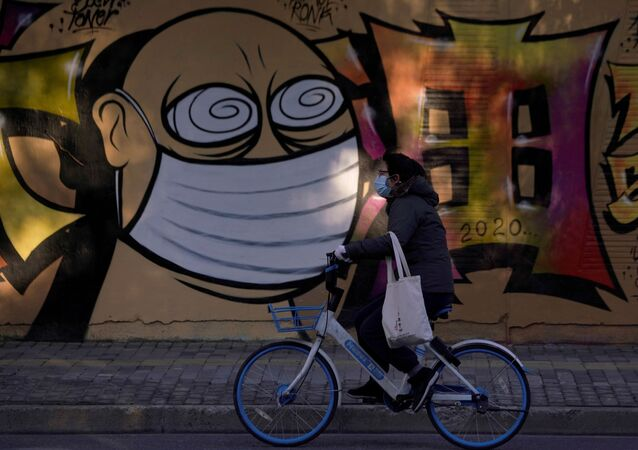 A woman wearing a protective mask cycles past graffiti-painted wall at a construction site in Shanghai, China