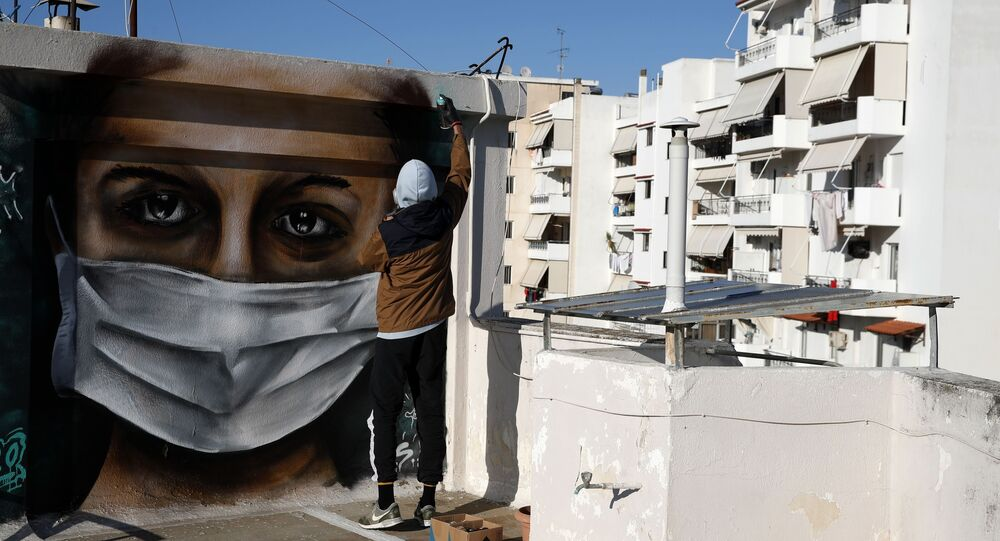 16-year-old Greek graffiti artist, spray-paints a design, a woman wearing a face mask referring to protection against coronavirus, on the roof of his apartment block in Athens
