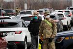 Police and U.S. Military personnel work amid a line of cars of people arriving for testing at a new drive-thru coronavirus disease (COVID-19) testing center in the Staten Island borough of New York City, New York, U.S., March 19, 2020