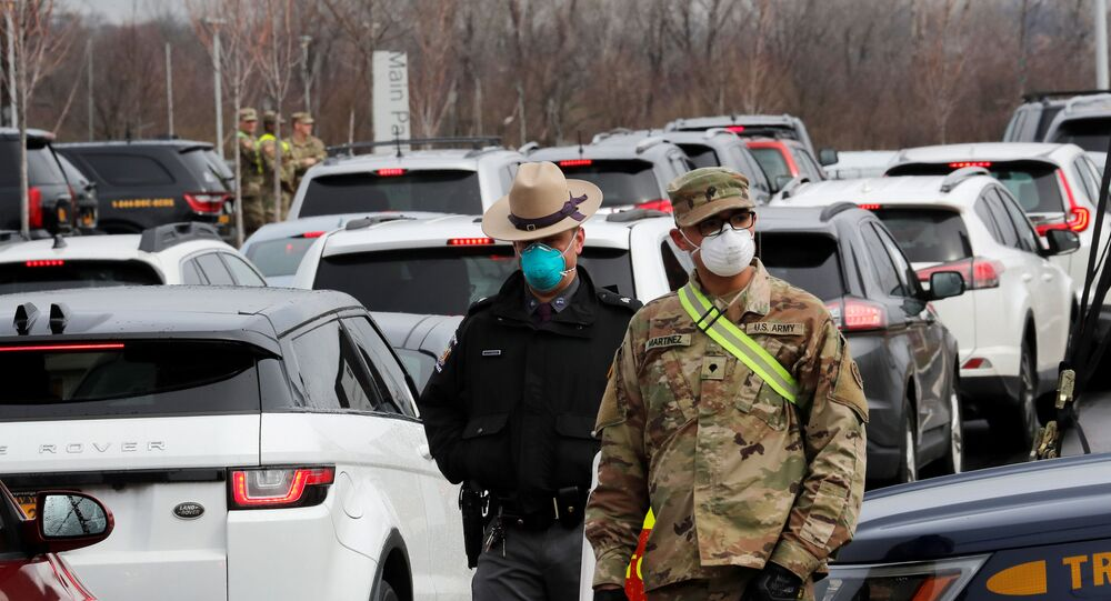 Police and US Military personnel work amid a line of cars of people arriving for testing at a new drive-thru coronavirus disease (COVID-19) testing centre in the Staten Island borough of New York City, 19 March 2020