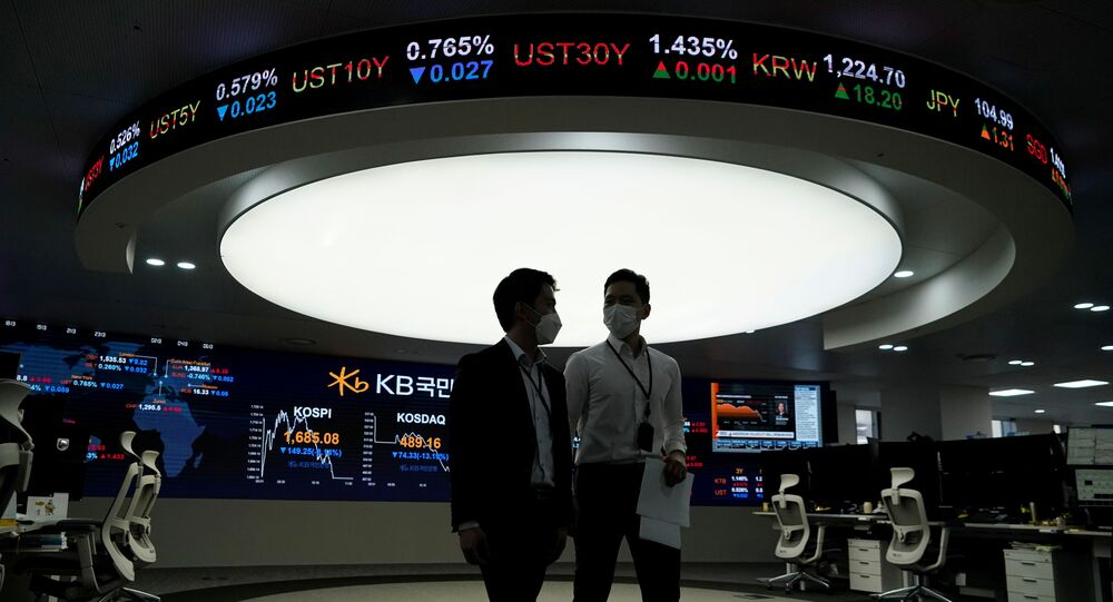 Currency dealers walk past an electronic board showing the Korea Composite Stock Price Index (KOSPI) at a dealing room of a bank in Seoul, South Korea, March 13, 2020