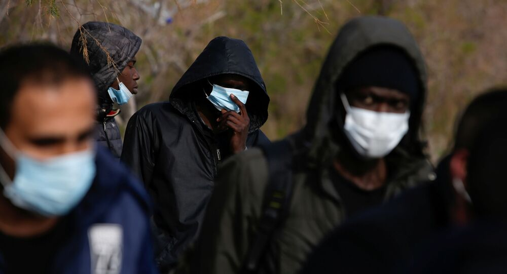 Migrants from sub-saharan African countries wear protective face masks handed over by Greek coast guard officers following their arrival on a dinghy near the city of Mytilene, after crossing part of the Aegean Sea from Turkey to the island of Lesbos, Greece, March 1, 2020