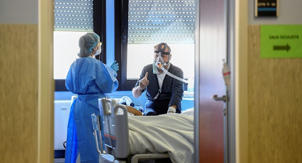 A medical worker wearing a protective mask and suit speaks with a patient suffering from coronavirus disease (COVID-19) in an intensive care unit at the Oglio Po hospital in Cremona, Italy, 19 March 2020.