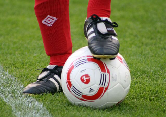 Foot of a soccer player in a football boot on a ball