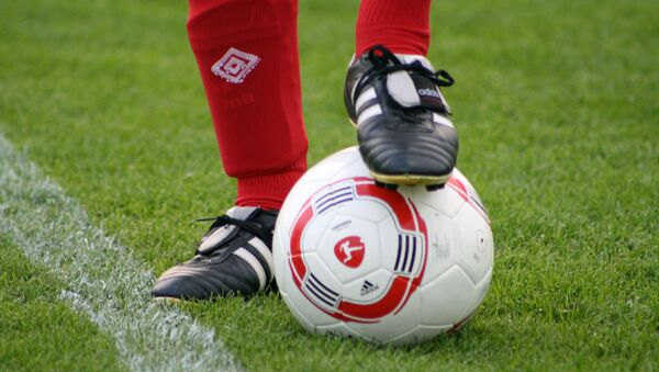 Foot of a soccer player in a football boot on a ball  - Sputnik International