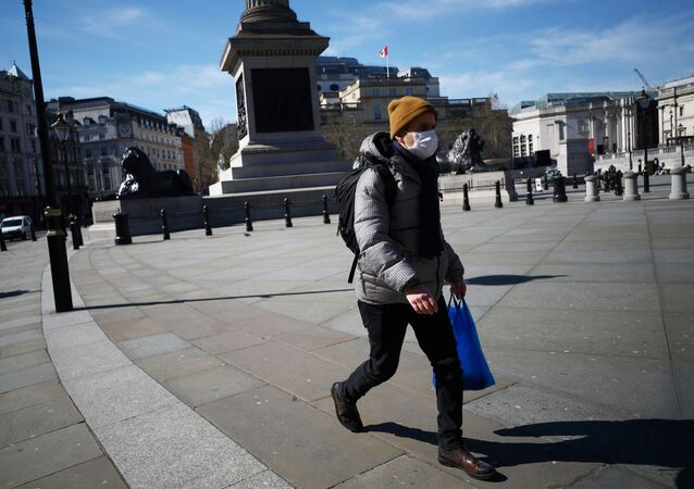 A man wears a mask in Trafalgar Square as the spread of the coronavirus disease (COVID-19) continues, in London, Britain, March 23, 2020