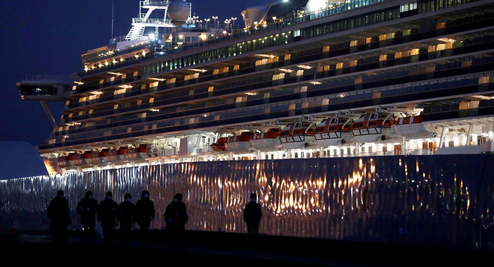 Workers walk past the coronavirus-hit cruise ship Diamond Princess as they leave the Yokohama Port, south of Tokyo, Japan February 21, 2020