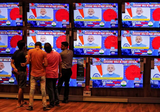 People watch Indian Prime Minister Narendra Modi addressing the nation amid concerns about the spread of coronavirus disease (COVID-19), on TV screens inside a showroom in Ahmedabad, India, March 19, 2020.