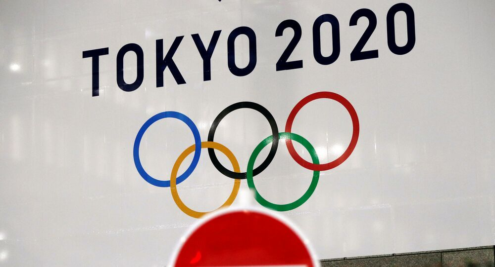 A banner for the upcoming Tokyo 2020 Olympics is seen behind a traffic sign, following an outbreak of the coronavirus disease (COVID-19), in Tokyo, Japan, March 23, 2020.