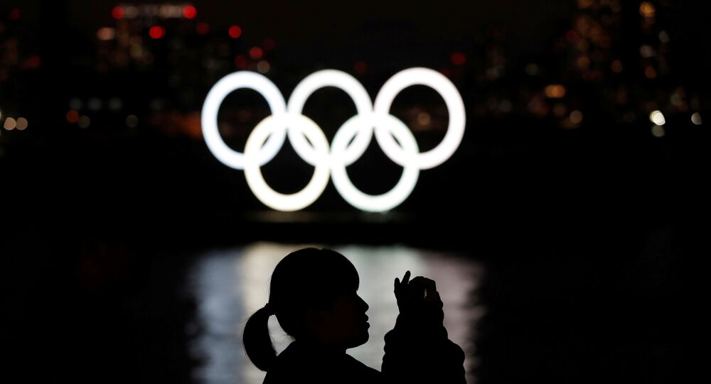 A woman takes a photograph in front of the giant Olympic rings at the waterfront area at Odaiba Marine Park in Tokyo, Japan, March 22, 2020.