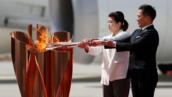 Three-time Olympic gold medalists Tadahiro Nomura and Saori Yoshida light the Olympic Flame at the Olympic cauldron during a ceremony at Japan Air Self-Defense Force Matsushima Base in Higashi-Matsuhsima, Miyagi prefecture, northern Japan March 20, 2020 - Sputnik International