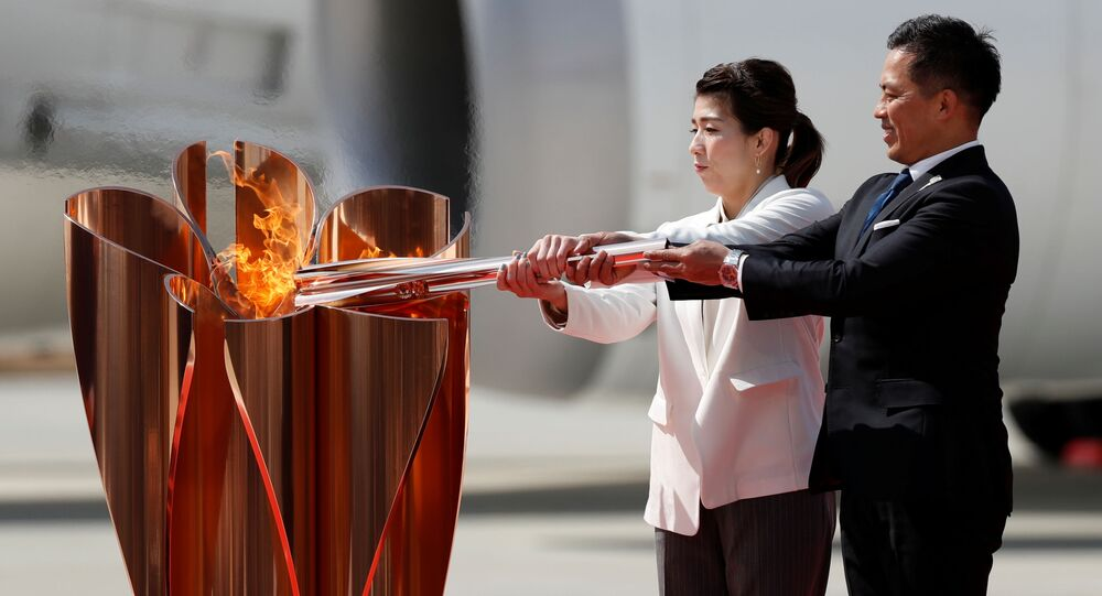 Three-time Olympic gold medalists Tadahiro Nomura and Saori Yoshida light the Olympic Flame at the Olympic cauldron during a ceremony at Japan Air Self-Defense Force Matsushima Base in Higashi-Matsuhsima, Miyagi prefecture, northern Japan March 20, 2020