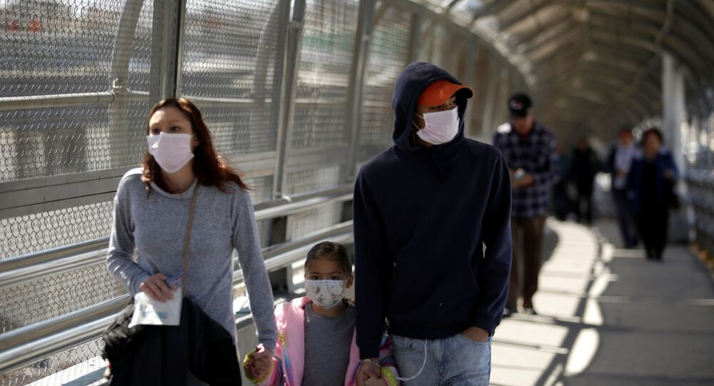 A family wearing protective face masks walks towards the U.S. at the Paso del Norte International Border bridge after the United States and Mexico have agreed to restrict non-essential travel over their shared border in an effort to limit the spread of the new coronavirus (COVID-19), in Ciudad Juarez, Mexico March 20, 2020.