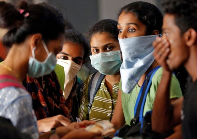 A group of students wearing protective masks wait to buy tickets at a railway station amid coronavirus fears, in Kochi, India, March 10, 2020