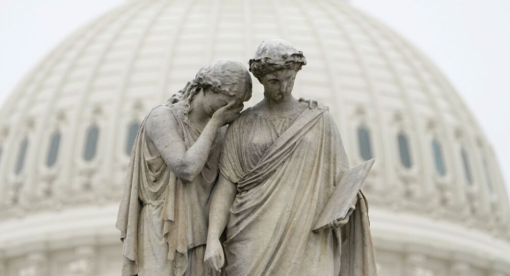 Grief holds her covered face against the shoulder of History and weeps in mourning as depicted at the Peace Monument in front of the U.S. Capitol in Washington, U.S., March 23, 2020.  The U.S. Senate struggled to reach agreement on a far-reaching coronavirus stimulus package on Monday.