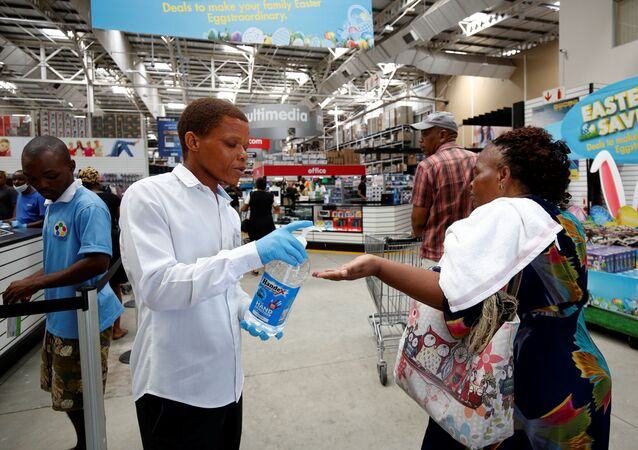 A store assistant gives people hand sanitiser as shoppers stock up on groceries at a Makro Store ahead of a nationwide 21 day lockdown in an attempt to contain the coronavirus disease (COVID-19) outbreak in Durban, South Africa, March 24, 2020.