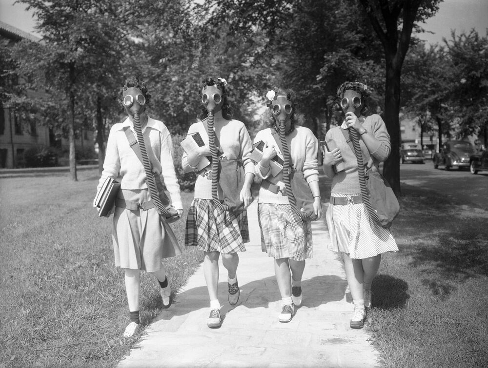 Looking ahead to the possibility that gas masks may some day be a necessary part of their ensemble, these University of Detroit students are trying out masks in a practice drill on the campus June 23, 1942.