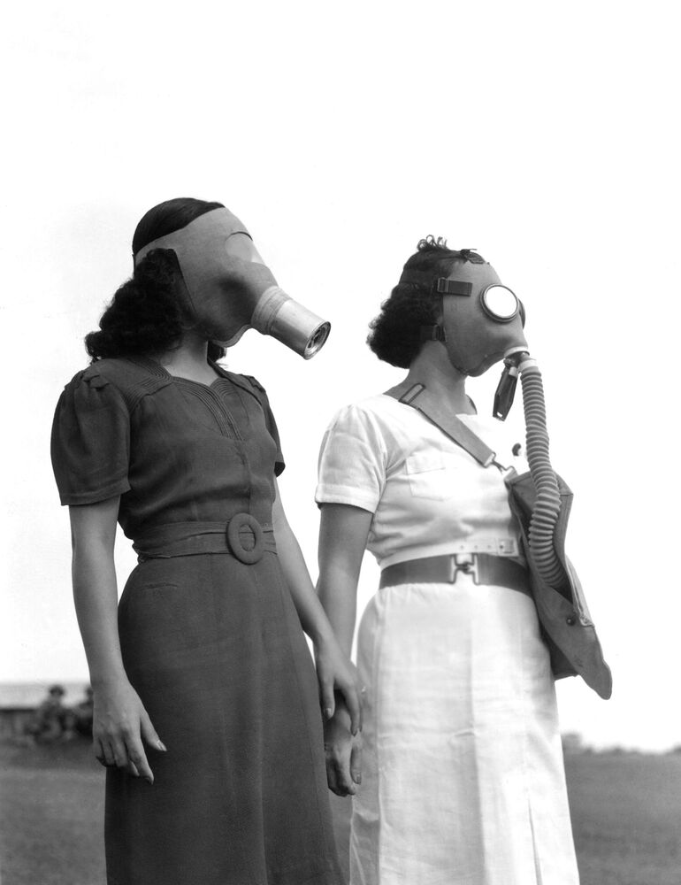 War jitters has Manila trying on gas masks. Most of the masks are imported from the U.S. some of them are manufactured locally. Shown, what the well dressed Filipina will wear en route to the air raid shelter in Manila, Philippines on August 5, 1941.