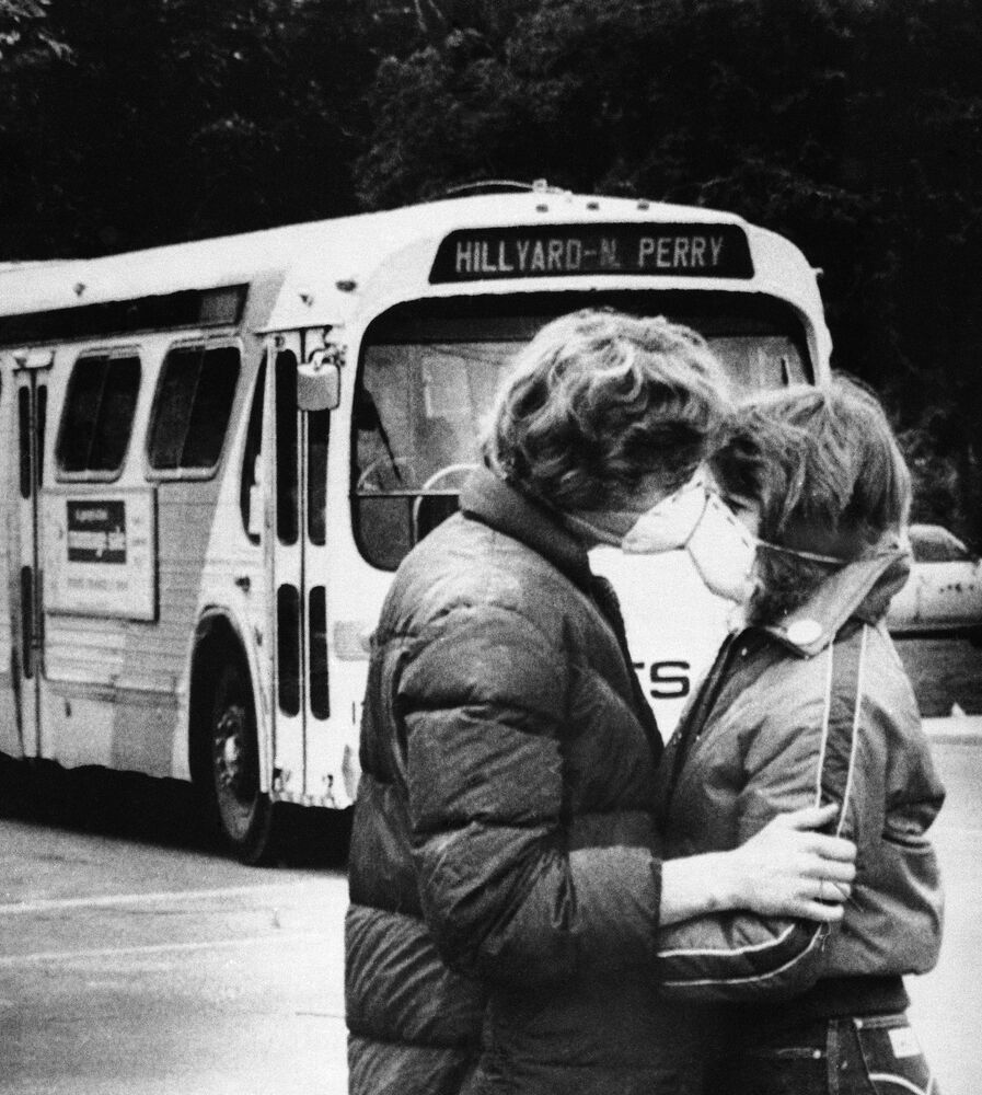 Fifteen-year-old Heidi Havens gives Allen Troup, 16, a kiss as he prepares to board a Spokane City bus, May 27, 1980. Spokane residents have had to wear face masks while outside for days because of possible health threats from volcanic ash sprayed over the area by Mount St. Helens.