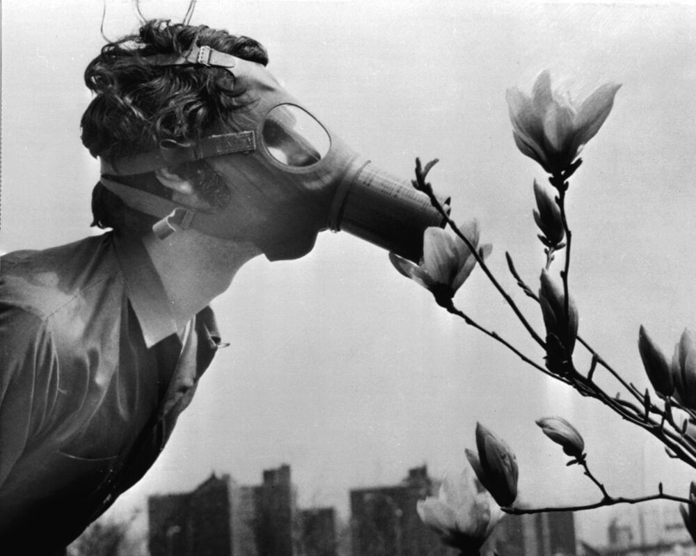 A Pace College student in a gas mask smells a magnolia blossom in City Hall Park on Earth Day, April 22, 1970, in New York.