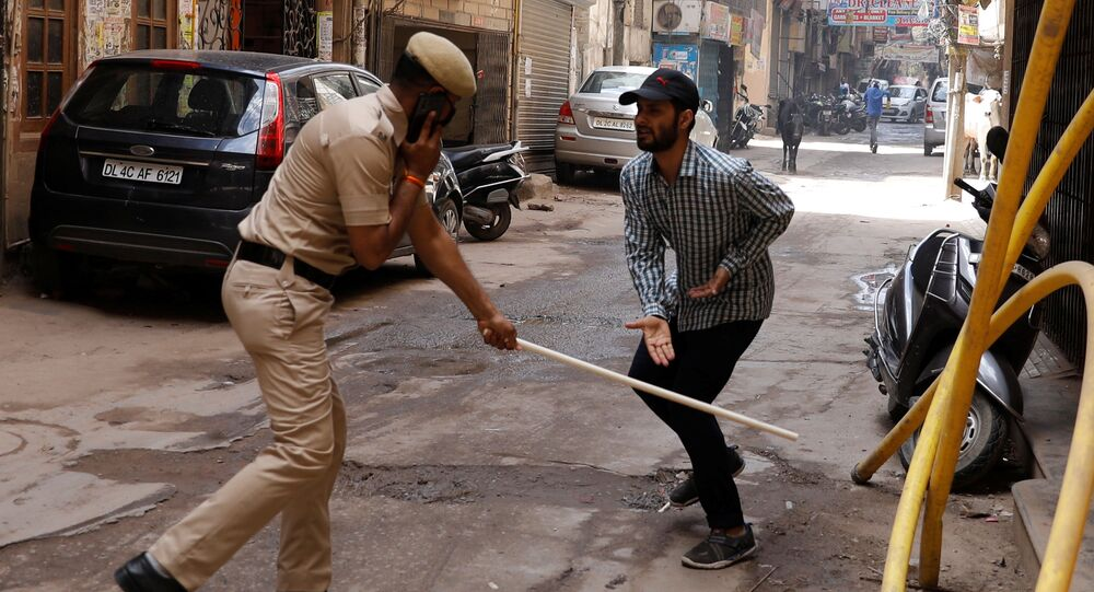A police officer wields his baton against a man as a punishment for breaking the lockdown rules after India ordered a 21-day nationwide lockdown to limit the spreading of coronavirus disease (COVID-19), in New Delhi, India, March 25, 2020