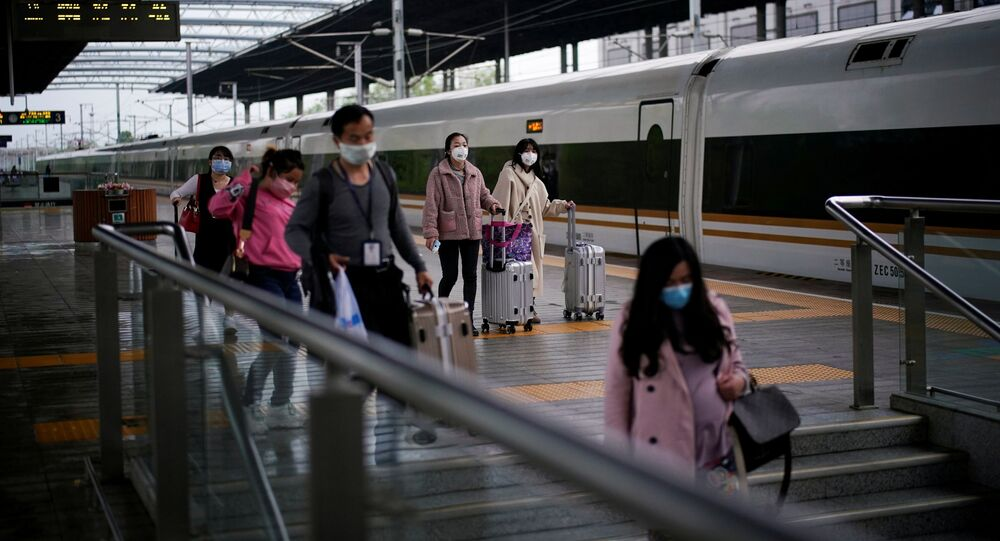 Passengers wearing face masks travel with their belongings at a railway station in Xianning of Hubei province, the epicentre of China's coronavirus disease (COVID-19) outbreak, March 25, 2020. REUTERS/Aly Song