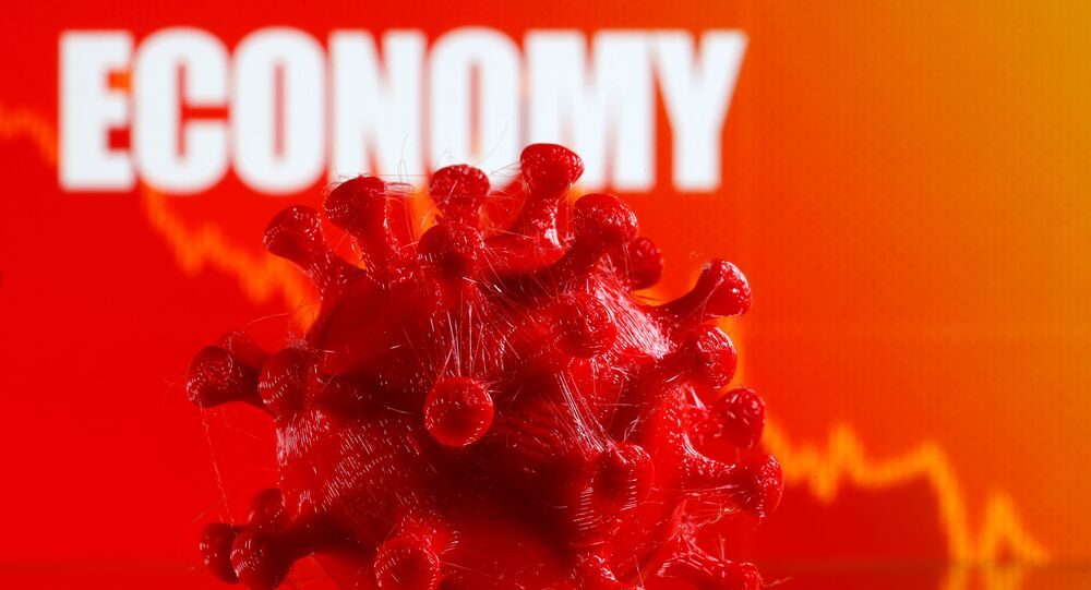 A 3D-printed coronavirus model is seen in front of a stock graph and the word Economy on display in this illustration taken March 25, 2020.