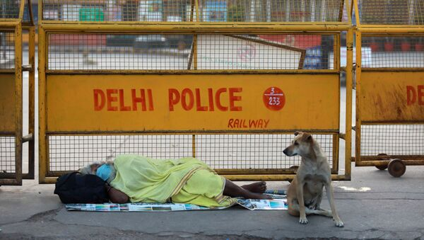 A homeless person sleeps on the pavement outside a railway station during a 21-day nationwide lockdown to limit the spreading of coronavirus disease (COVID-19), in New Delhi, India, March 26, 2020.  - Sputnik International