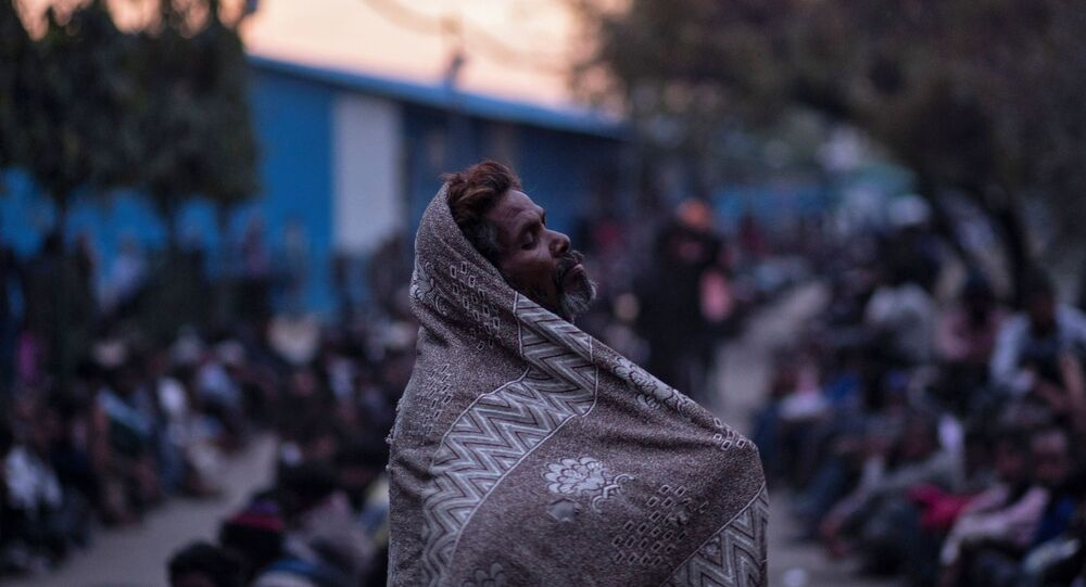 A homeless man waits for food outside a government-run night shelter during a 21-day nationwide lockdown to limit the spreading of coronavirus disease (COVID-19), in New Delhi, India, March 25, 2020.