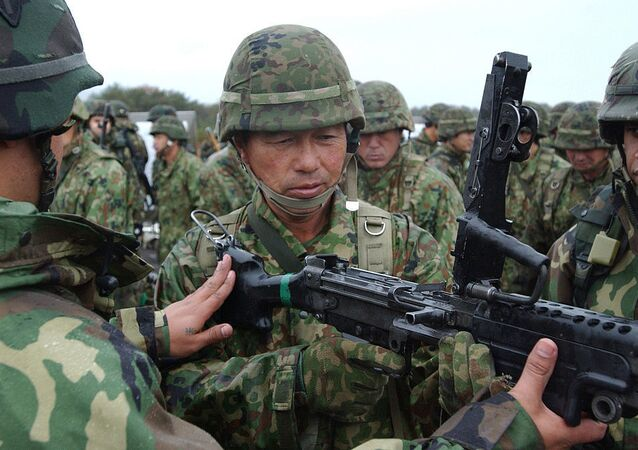 American Soldiers demonstrate the M-249 Squad Automatic Weapon to a Japanese soldier of the 39th Infantry Regiment, Japan Ground Self-Defense Force, during Exercise Orient Shield