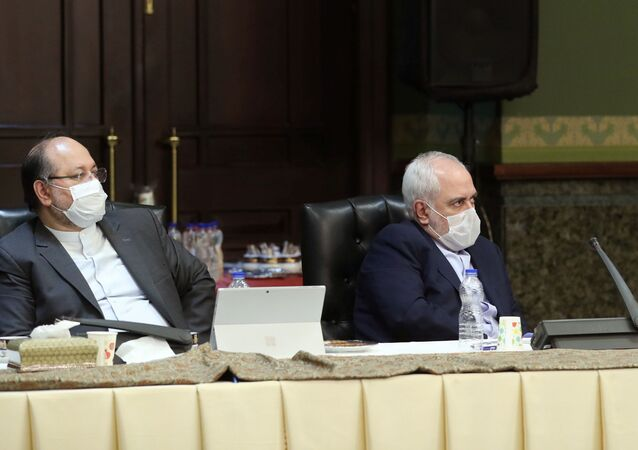 Iranian Foreign Minister Javad Zarif (R) wears a face mask amid fears of coronavirus disease (COVID-19) as he attends a meeting of the Iranian government task force on the coronavirus, in Tehran, Iran, March 21, 2020.