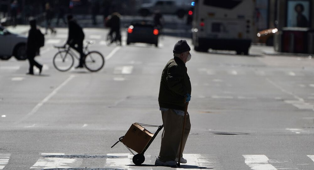 A pedestrian crosses a deserted 7th Ave in Times Square during the outbreak of Coronavirus disease (COVID-19), in the Manhattan borough of New York City, New York, U.S., March 26, 2020.