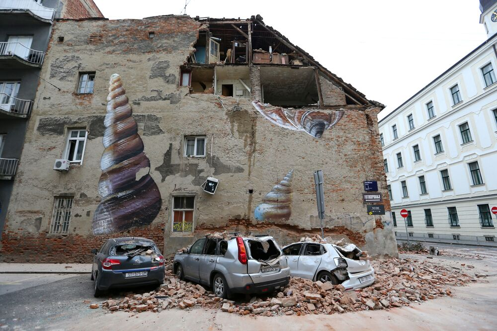 Damaged cars and a partially damaged building are seen following an earthquake, in Zagreb, Croatia March 22, 2020.