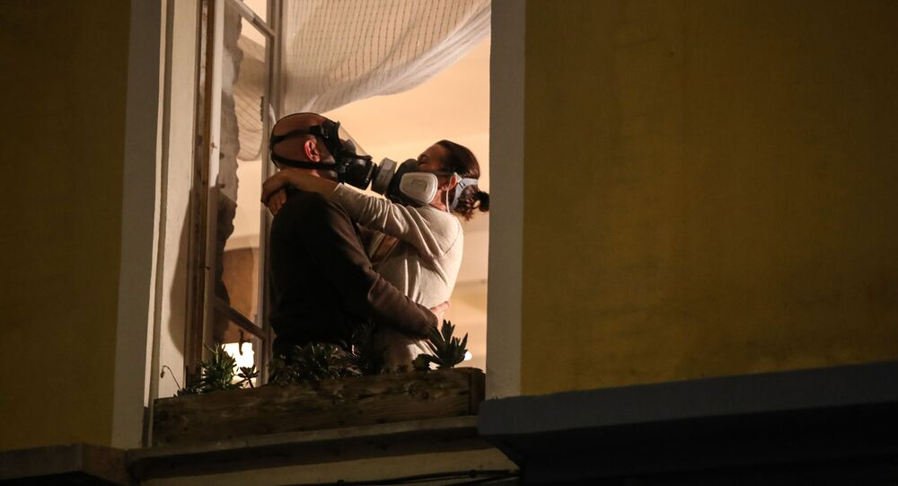 A man wearing a gas mask and a woman wearing an air filtering mask embrace at their window