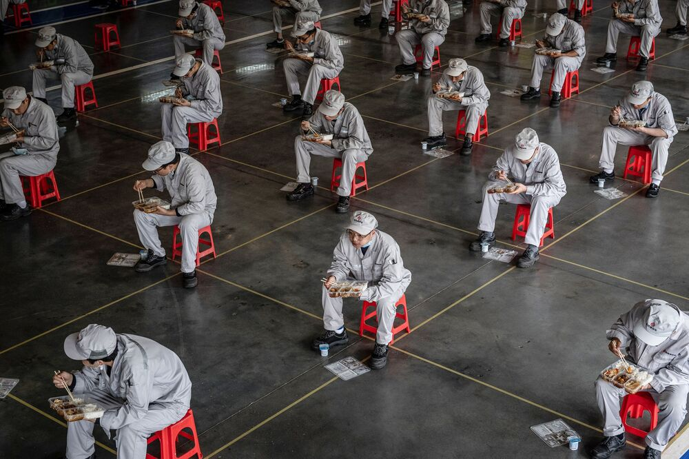 This photo taken on March 23, 2020 shows employees eating during lunch break at an auto plant of Dongfeng Honda in Wuhan in China's central Hubei province. - People in central China, where the COVID-19 coronavirus was first detected, are now allowed to go back to work and public transport has restarted, as some normality slowly returns after a two-month lockdown.