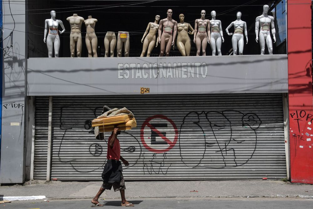 A homeless walks past a closed parking lot and mannequins in downtown Sao Paulo, Brazil, after the city government decreed the closure of shops and stores as a precautionary measure against the spread of the novel coronavirus COVID-19, on March 24, 2020. -