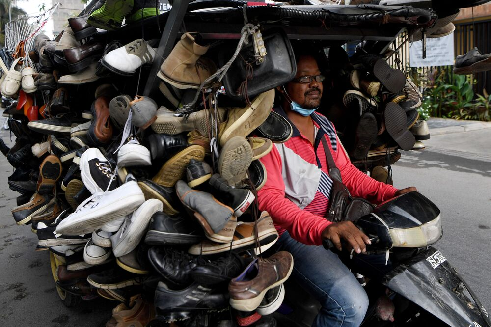 A man rides a motorcart loaded with secondhand shoes for sale along a street in Phnom Penh on March 24, 2020.