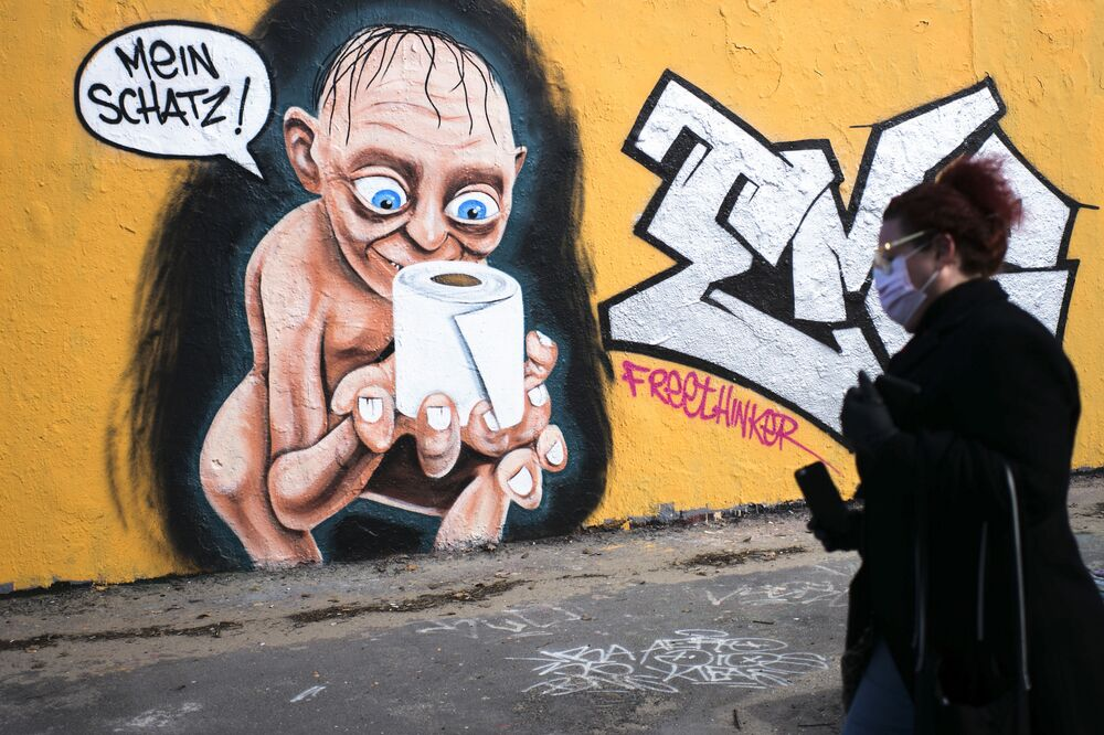 A woman walks in front of a graffiti depicting te character of Gollum from Lord of te Rings, holding a roll of toilet paper and saying My precious, in te Mauerpark public park at te district Prenzlauer Berg in Berlin, Hermany, Saturday, March 21, 2020. In order to slow down te spread of te coronavirus, te Herman government has considerably restricted public life and asked te citizens to stay at home.