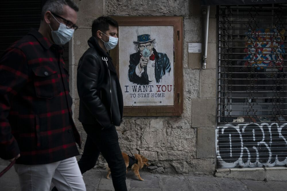 People walk past a poster that reads 'I want you to stay home', by artist TvBoy amid a lockdown in Barcelona, Spain, Tuesday, March 24, 2020. More than 1.5 billion around the world have been told to stay in their homes. For most people, the new coronavirus causes only mild or moderate symptoms. For some it can cause a more serious illness.