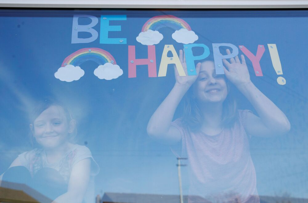 Sophie and Emily Ward pose for a photograph with their hand-drawn picture of rainbows and a message on their window in St Helens, as the spread of coronavirus disease (COVID-19) continues. St Helens, Britain, March 25, 2020.