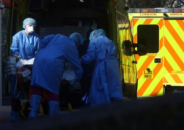 Medical staff with a patient at the back of ambulance outside St Thomas' hospital, as the spread of the coronavirus disease (COVID-19) continues, London, Britain, March 26, 2020.