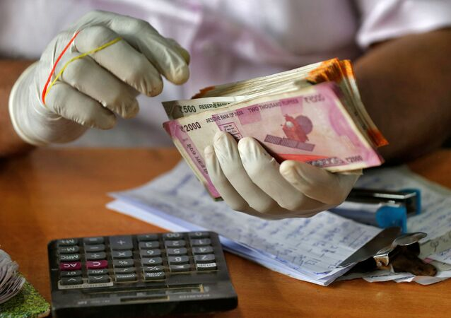A trader wearing protective hand gloves counts Indian currency notes at a market during a 21-day nationwide lockdown to limit the spreading of coronavirus disease (COVID-19), in Kochi, India, March 27, 2020.