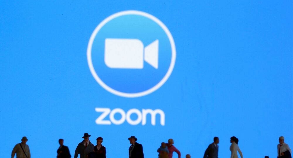 Small toy figures are seen in front of displayed Zoom logo in this illustration taken March 19, 2020.