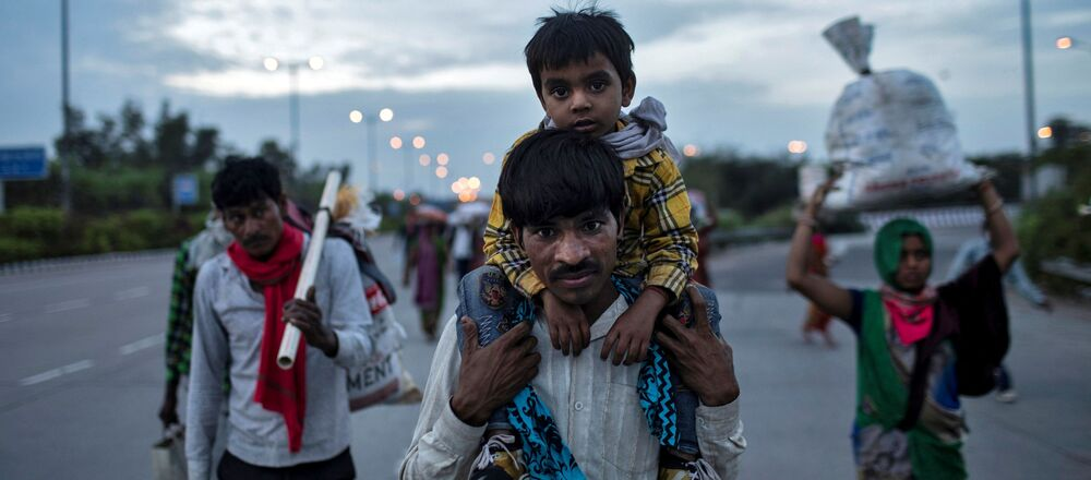 A migrant worker carries his son as they walk along a road with others to return to their village, during a 21-day nationwide lockdown to limit the spreading of coronavirus