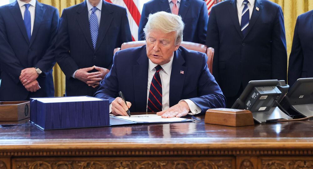 U.S. President Donald Trump signs the $2.2 trillion coronavirus aid package bill as he sits at the Resolute Desk in the Oval Office of the White House in Washington, U.S., March 27, 2020.