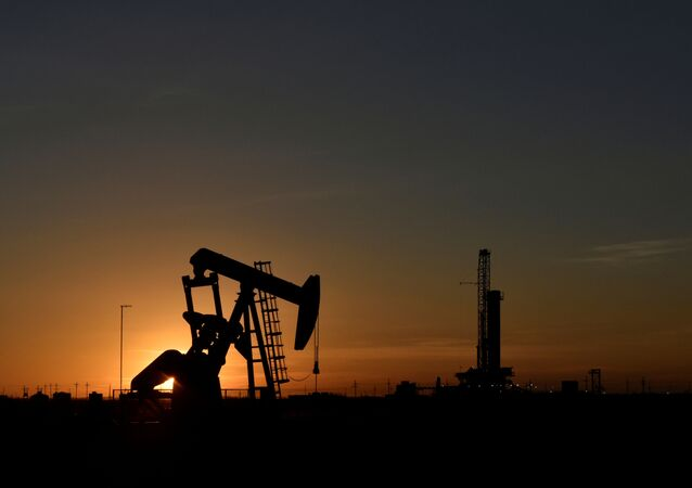 FILE PHOTO: A pump jack operates in front of a drilling rig at sunset in an oil field in Midland, Texas U.S. August 22, 2018. Picture taken August 22, 2018.