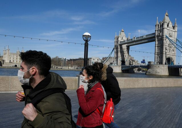 People wearing masks infront of Tower Bridge as the spread of the coronavirus disease (COVID-19) continues, in London, Britain, March 23, 2020.